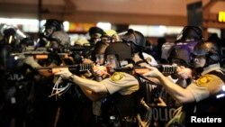 Police officers point their weapons at demonstrators protesting the shooting death of Michael Brown in Ferguson, Missouri, on August 18.