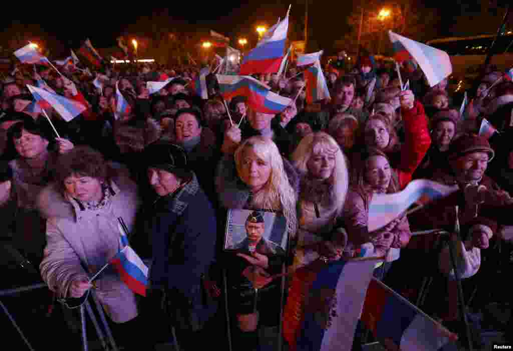 A woman holds a portrait of Russia's President Vladimir Putin as others wave Russian flags as the preliminary results of referendum on Crimea joining Russia are announced on March 16. (Reuters/Baz Ratner)