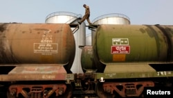 India -- A worker walks atop a tanker wagon to check the freight level at an oil terminal on the outskirts of Kolkata, November 27, 2013