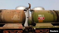 A worker walks atop a tanker wagon to check the freight level at an oil terminal on the outskirts of Kolkata. File photo