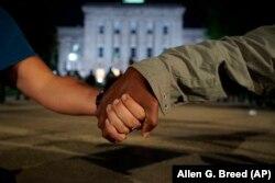 Dy protestues në SHBA – një me ngjyrë dhe një i bardhë – janë kapur për dore, teksa kërkojnë drejtësi për vdekjen e George Floyd.