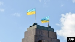 Steaguri ucrainene pe soclul statuii lui Lenin dărîmată de protestatari la Harkov cu o noapte înainte, 29 septembrie 2014.