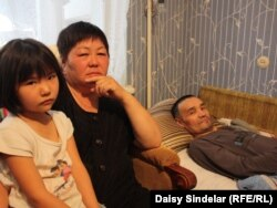 In June 2011, Yryskul is looking a bit better (with his wife, Karamat, and their daughter).