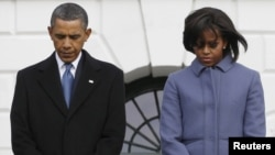 U.S. President Barack Obama and First Lady Michelle Obama take part in the moment of silence.