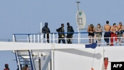 Somali pirates and some of the crewmembers on the upper deck aboard the Belize-flagged Ukrainian cargo MV Faina off of Somalia's coast as seen from a US Navy ship on 03Oct