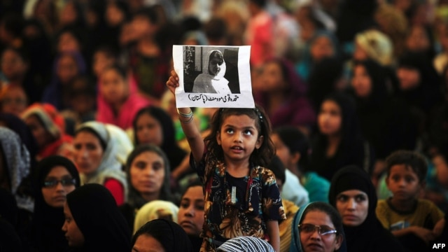 A girl holds a photograph of Malala Yousafzai aloft during a rally in Karachi on October 10.