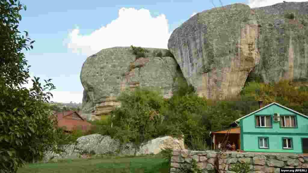 Отделившаяся скала нависает прямо над туристическим домиком