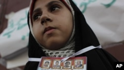 An Egyptian protester with pictures of Egyptians killed during the revolution takes part in a demonstration in Suez on July 8.