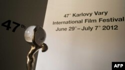 Czech Republic -- The Crystal Globe Award trophy is seen in front of a sign presenting the 47th Karlovy Vary International Film Festival (KVIFF), 28Jun2012