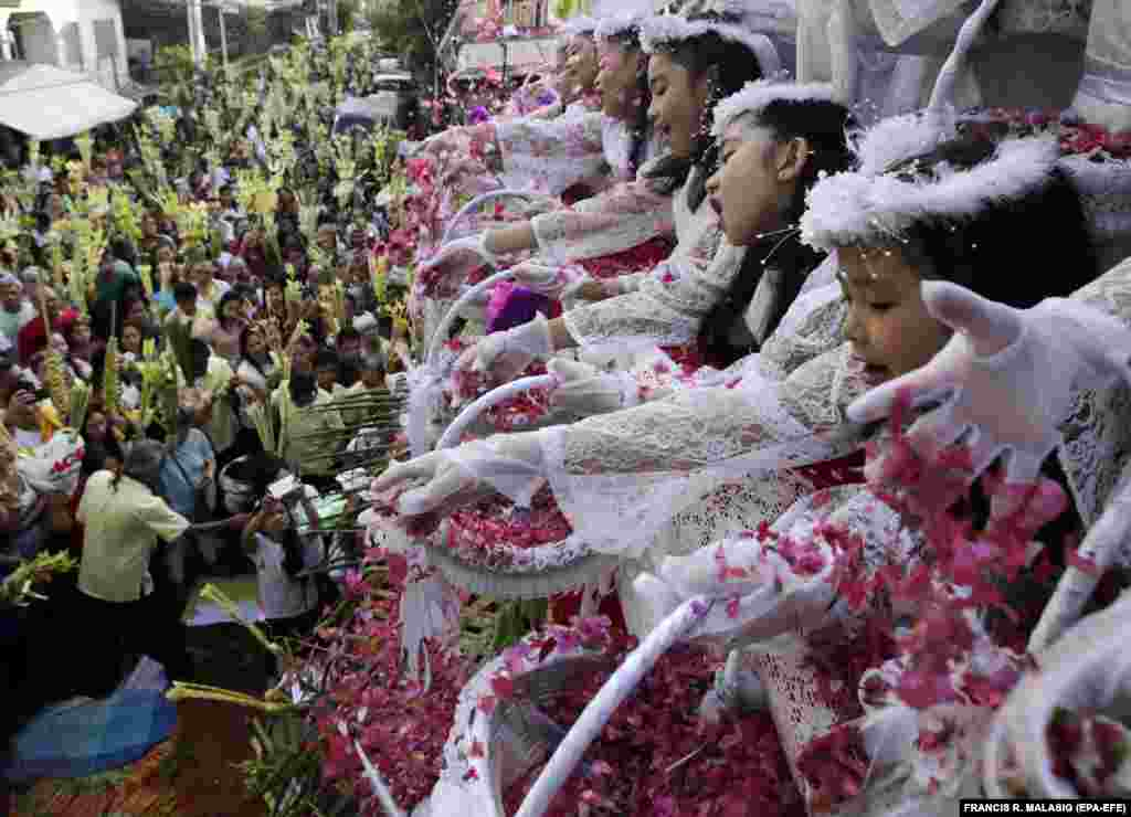 Filipino children shower flower petals onto Catholic devotees holding decorative palm fronds during a procession to mark Palm Sunday in Las Pinas City, south of Manila, on April 14. (epa-EFE/Francis R. Malasig)