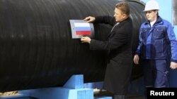 Gazprom Chief Executive Aleksei Miller attaches the Russian national flag to a pipe of the Nord Stream pipeline near the town of Vyborg in April. The pipeline should bring Russian gas directly to Germany, bypassing transit countries.