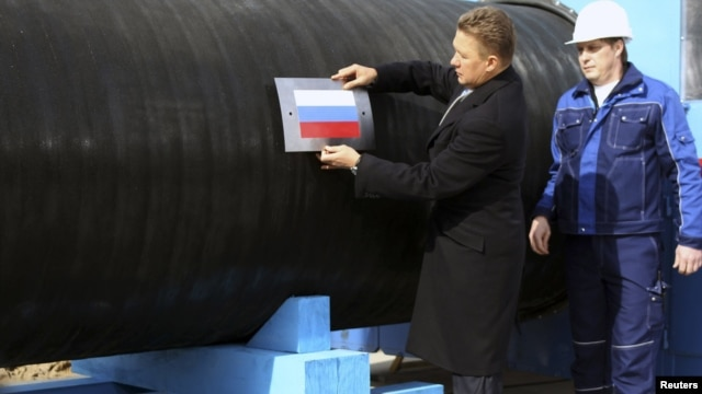 Gazprom CEO Aleksei Miller attaches a Russian flag to a pipe of the Nord Stream pipeline near Vyborg, Russia. The EU is now looking to make the gas giant play by its rules in Europe.