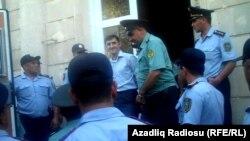 Әзербайжан құқық қызметкерлері «Мусават» партиясы жастар ұйымының төрағасы Турал Аббаслыны (ортада) сот залынан алып шығып келеді. Баку, 12 тамыз 2011 ж.