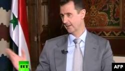 Башар аль-Асад, кард із його попередньої появи на телебаченні в інтерв'ю російському телеканалові RT, 8 листопада 2012 року