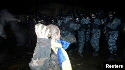 Сот ғимаратының алдында арнайы жасаққа тас лақтырғалы жатқан шеруші. Киев, 10 қаңтар 2014 жыл.