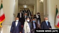 """Иран сыртқы істер министрі Мохаммад Жавад Зариф (оң жақта) пен """"Талибан"""" қозғалысының саяси жетекшісі Абдул Ғани Барадар (ортада) биыл қаңтарда Тегеранда кездескен."""