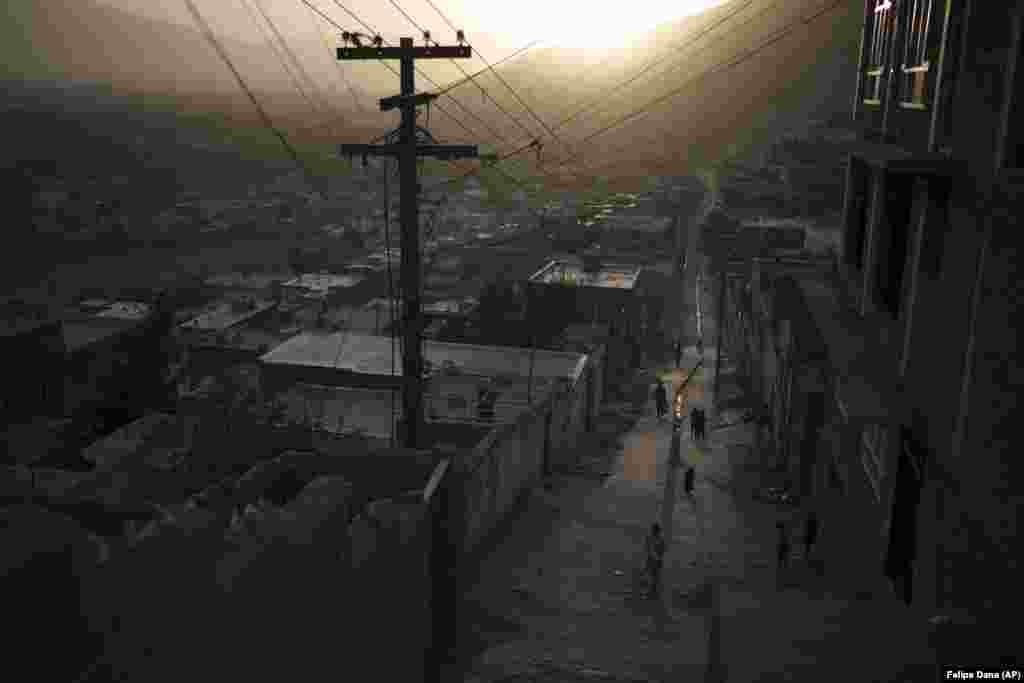 Afghans walk in an alleyway as the sun sets in Kabul.