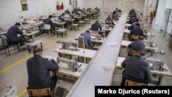 Колония в Сербии. В тюремном цеху заключенные шьют защитные маски для собственных нужд. Все работающие в масках и соблюдают дистанцию