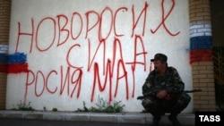 Сепаратист біля неграмотної «реклами» Новоросії, фото 23 червня 2014 року, Металіст Луганської області