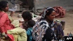 Pakistan -- A Pakistani woman (L) sits on a charpoy with others as she smokes at a slum in Lahore, 21Feb2012