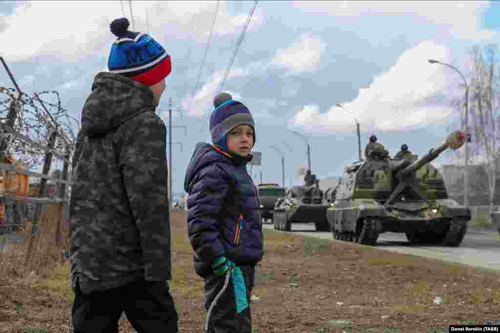 Boys watch self-propelled howitzers passing by during a rehearsal of a military parade in Yekaterinburg on April 14.