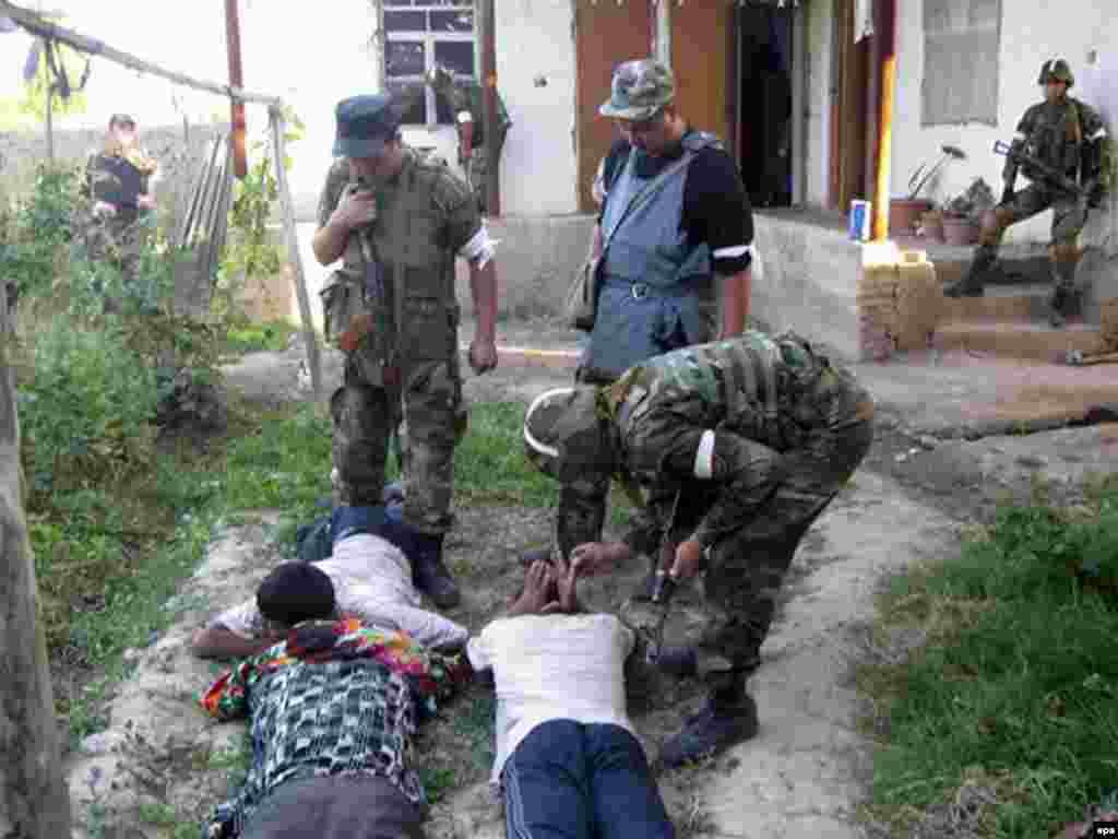 Қырғызстан ішкі істер министрлігінің өкілдері Оштағы үйлерді тінтіп жүр. 21 маусым 2010 жыл.