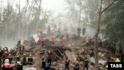 Rescuers and firefighters search the rubble left of an apartment block following a blast in Moscow in September 1999.