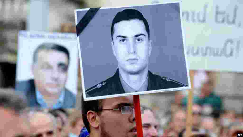 Hungarian demonstrators hold up a photo of Armenian Army Lieutenant Gurgen Margarian in front of the parliament building in Budapest, after his murderer was pardoned in Azerbaijan. (AFP/Attila Kisbenedek)