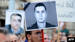 Hungary -- Activists and sympathizers of Hungarian 'Milla' Group lift a photo of Armenian Army Lieutenant Gurgen Margarian (C), beside a picture of Hungarian Prime Minister Viktor Orban (L), in front of parliament building in Budapest, 04Sep2012