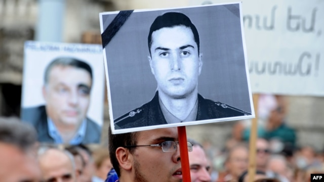 Demonstrators in Hungary hold up a photo of Armenian Army Lieutenant Gurgen Margarian (right) in front of the parliament building in Budapest on September 4 at a protest against the repatriation of Ramil Safarov.
