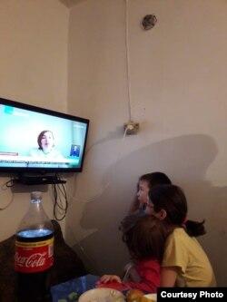 Akbota Abişbaýewanyň çagalary telewizora tomaşa edýärler. Maşgala arhiwiniň suraty.