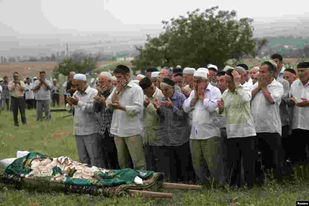 Mourners gather for the Estemirova's funeral in Koshkeldy, about 70 kilometers east of Grozny on July 16, 2009.