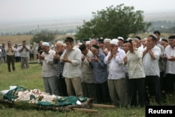 The funeral of Natalya Estemirova at a cemetery in Koshkeldy, 70 kilometers east of Grozny, on July 16, 2009.