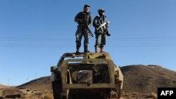 Ауған полицейлері совет әскерінен қалған көліктің қаңқасына шығып, төңіректі шолып тұр. Ауғанстан, 13 желтоқсан 2012 жыл.
