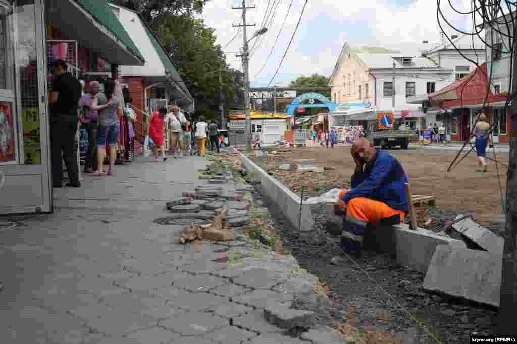 Часть деревьев, которые мешали расширению улицы, спилили.Рабочие старательно укладывает новый бордюр, 16 июля 2015 года