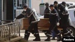 Құтқарушылар Алжирдегі оқиғада кепілге алынған адамның мәйітін табытқа салып, әкетіп барады. Алжир, 21 қаңтар 2013 жыл.