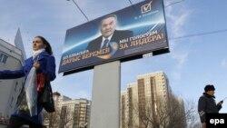 Молодая женщина с цветами проходит мимо предвыборного билборда Нурсултана Назарбаева. Астана, 31 марта 2011 года. Иллюстративное фото.