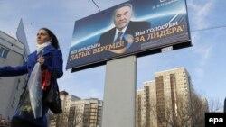 Нұрсұлтан Назарбаевтың сайлау алды билборды маңынан өтіп бара жатқан әйел. Астана, 31 наурыз 2011 жыл. (Көрнекі сурет)