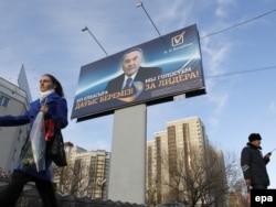 Президент сайлауында Нұрсұлтан Назарбаевқа дауыс беруге шақырған баннердің жанынан өтіп бара жатқан әйел. Астана, 31 наурыз 2011 жыл.