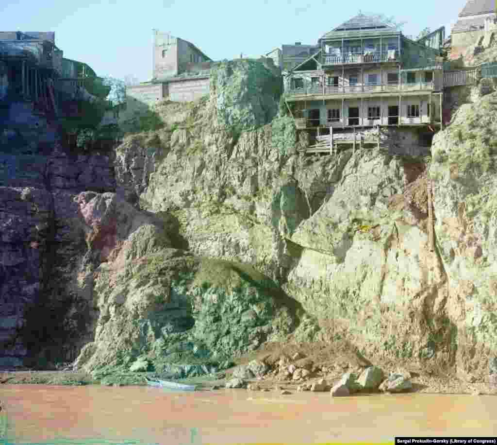 Дом на вершине скалы в Тбилиси, с опасной тропой, ведущей к реке и лодке. Из трубы справа в реку Мтквари сбрасываются сточные воды
