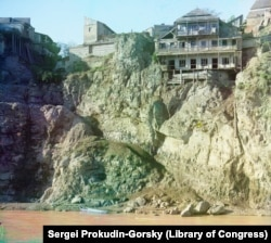 A clifftop house in Tbilisi with what appears to be a precarious pathway leading down to the river and a boat. A pipe on the right is dribbling wastewater into the Mtkvari River.