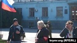 Захват Крыма,Симферополь, 3 марта 2014, на заднем плане – вооруженный человек в форме без знаков различия