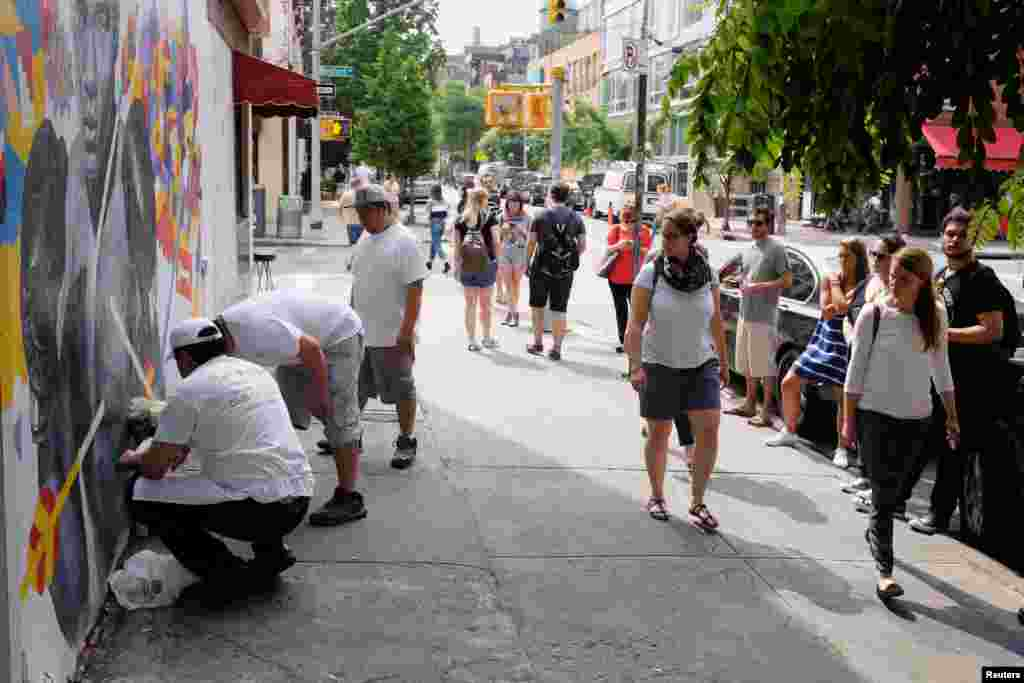 Сотрудники Joe's Pizza соорудили мемориал рядом с фреской в Нью-Йорке, США.