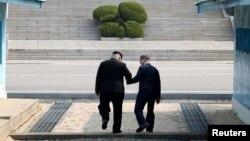 Лідер КНДР Кім Чен Ин (ліворуч) та Південної Кореї Мун Чжен Ін під час першої зустрічі в демілітаризованій зоні. Пханмунджом, квітень 2018 року