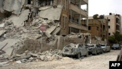 A building and vehicles that were damaged following blasts in the city of Idlib on April 30.