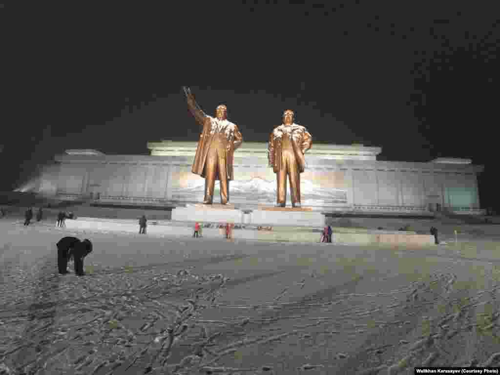 Гигантские бронзовые памятники Ким Ир Сену и Ким Чен Иру на холме Мансу в Пхеньяне. За монументом - здание музея Революции.