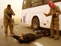 Iraqi security forces detain an alleged militant in Al-Najaf on January 28