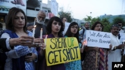 Activists of Human Rights Commission of Pakistan hold candles and placards during a protest against the killing of lawyer Rashid Rehman in Islamabad.
