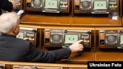 Депутат Верховной Рады нажимает на кнопку голосования.