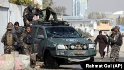 Afghan security personnel inspect the site of suicide attack near the election commission office in Kabul on October 29.